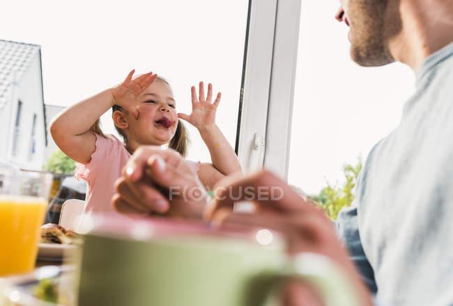 Девушка высовывает язык на отца дома — стоковое фото