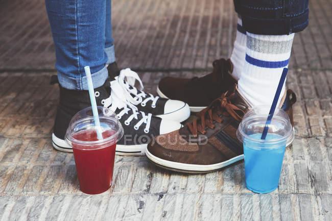 Bicchieri di plastica con bevande analcoliche in piedi oltre a piedi delle giovani coppie — Foto stock