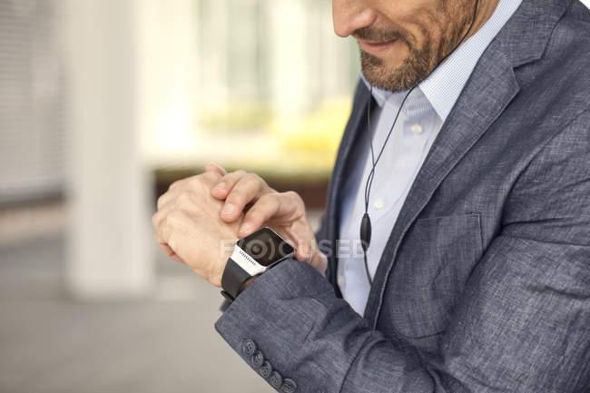 Nahaufnahme eines Geschäftsmannes, der sich Smartwatch ansieht — Stockfoto