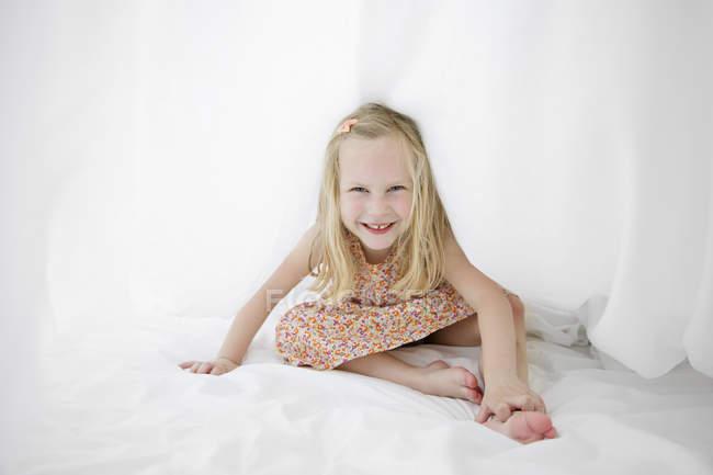 Porträt eines lächelnden blonden Mädchens auf einem weißen Bett, das sich unter einem Laken versteckt — Stockfoto
