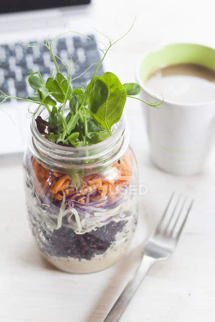 Rainbow salad in jar with mug of coffee and laptop — Stock Photo