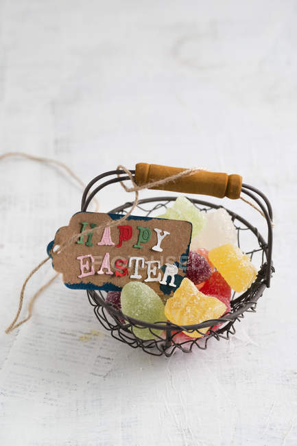 Frohe Osteranhänger auf Korb mit Gelee-Eiern — Stockfoto