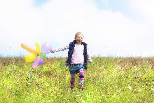 Young girl running with balloons over meadow — Stock Photo
