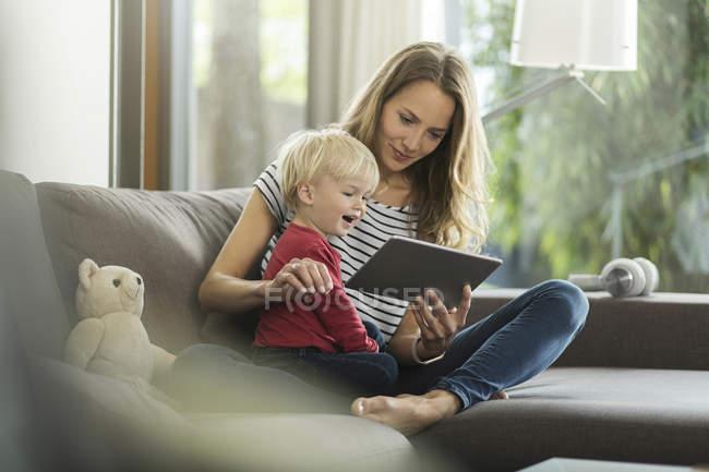 Мати і син на дивані з цифровий планшетний — стокове фото