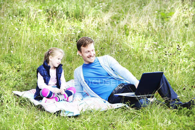 Father and daughter sitting on meadow, father working on laptop — Stock Photo