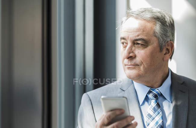 Leitender kaukasischer Geschäftsmann mit Mobiltelefon — Stockfoto