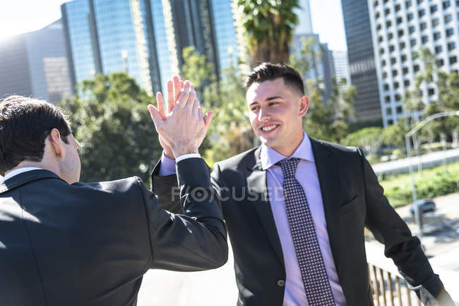 Two businessmen giving high five in city street — Stock Photo