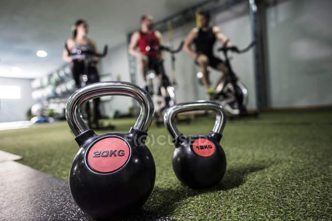 Kettlebells in Turnhalle mit Menschen eine Ausbildung am Heimtrainer auf Hintergrund — Stockfoto