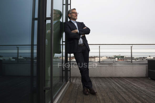 Успішний бізнесмен, стоячи на терасі office, дивлячись задоволені — стокове фото