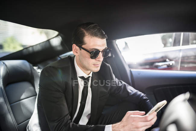 Businessman in car using cell phone — Stock Photo