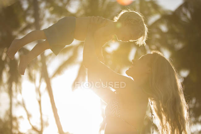 Happy mother lifting up her son in backlight — Stock Photo