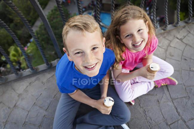 Портрет брат і сестра з конуси морозива, сидячи на балконі, дивлячись на камеру — стокове фото