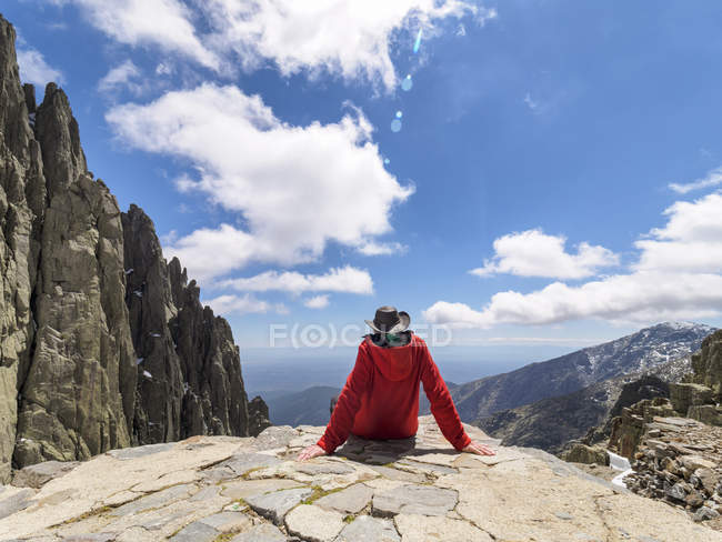 Spain, Sierra de Gredos, rear view of hiker sitting on rock, mountains landscape view on background — Stock Photo