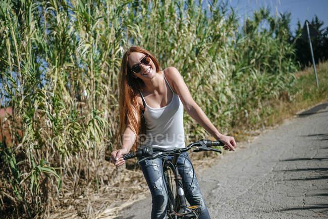 Glückliche junge Frau Reiten Fahrrad auf Feldweg — Stockfoto