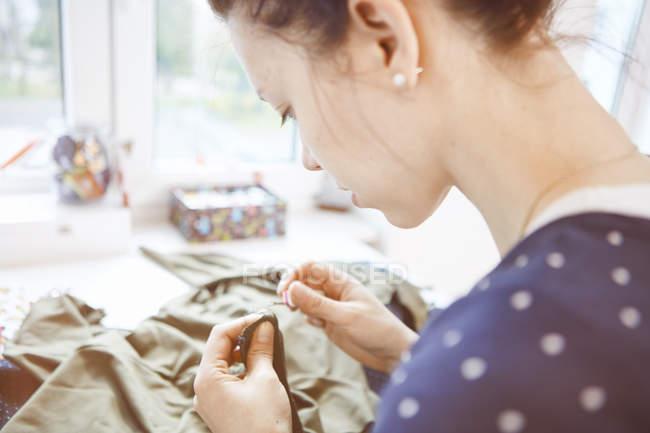 Jovem mulher costura costura — Fotografia de Stock