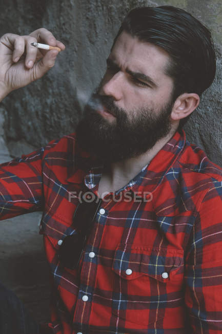 Portrait of smoking serious looking man with full beard — Stock Photo