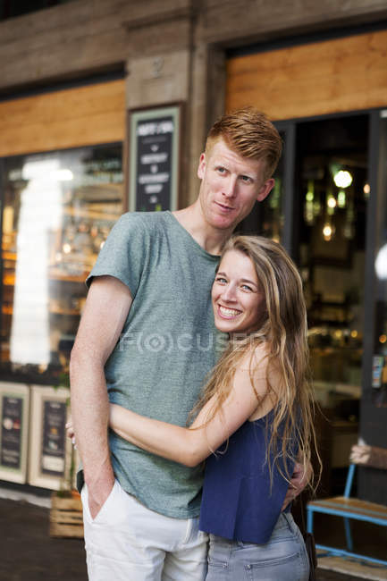 Portrait of happy couple standing in front of a coffee shop — Stock Photo