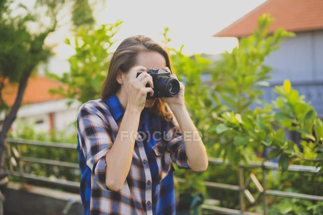 Mulher usando câmera vintage — Fotografia de Stock