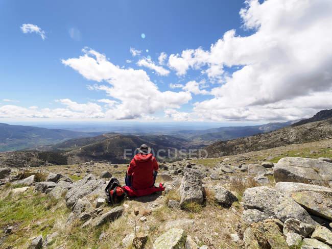 Spain, Sierra de Gredos, Rear view of hiker sitting on mountain plateau — Stock Photo
