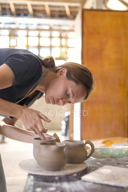 Гончар в мастерской работает над глиняной банкой — стоковое фото