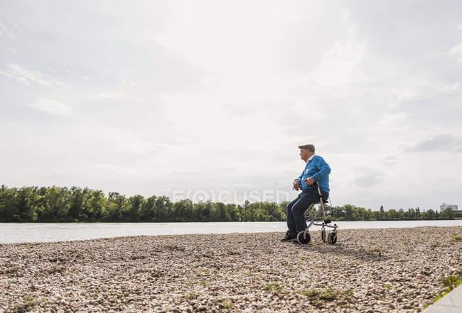 Senior man sitting on wheeled walker at riverside — Stock Photo