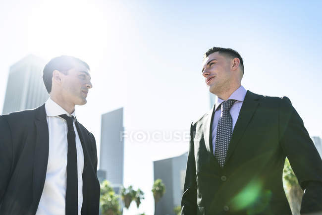 Two businessmen in backlight, cityscape on background — Stock Photo