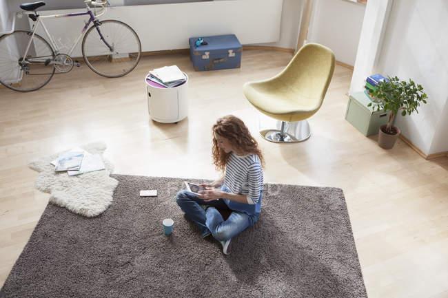 Donna a casa che si siede sul pavimento per mezzo della compressa di digital — Foto stock