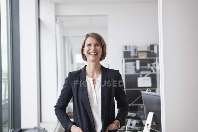 Laughing businesswoman standing in modern office — Stock Photo