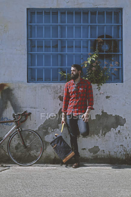 Man and racing cycle leaning against facade — Stock Photo