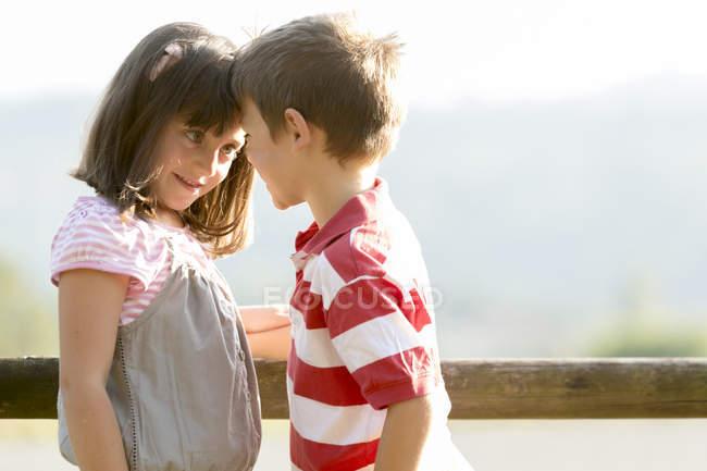 Menino e menina de pé cara a cara perto de cerca de madeira — Fotografia de Stock