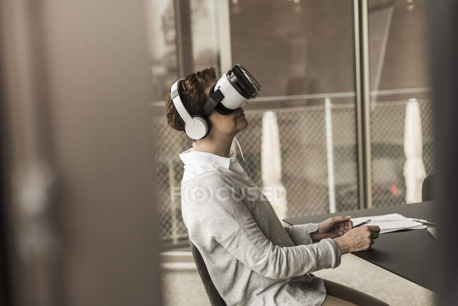 Woman in office wearing virtual reality glasses — Stock Photo