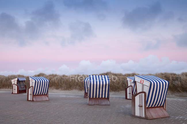 Німеччина, Нижня Саксонія, Східної Фризії, Nordstrand, пляж з пляжу дахівками плетеними стільцями, afterglow — стокове фото