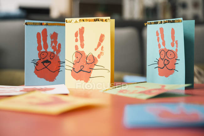 Self-made Easter bunny cards with handprints on a table — Stock Photo