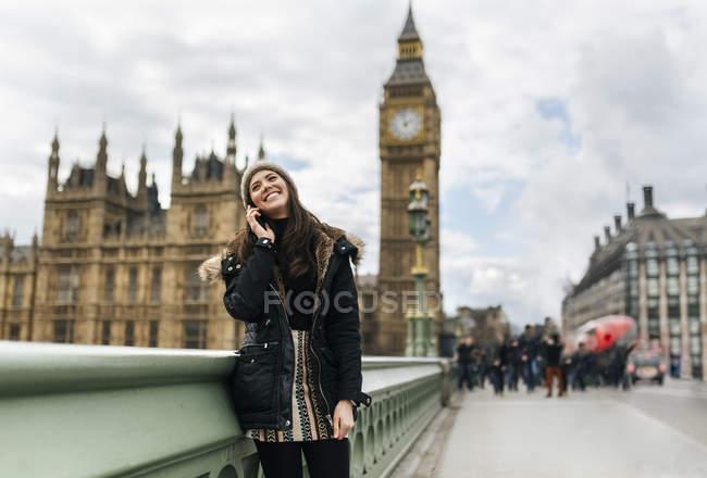Reino Unido, Londres, joven feliz telefoneando con teléfono inteligente frente al Palacio de Westminster - foto de stock