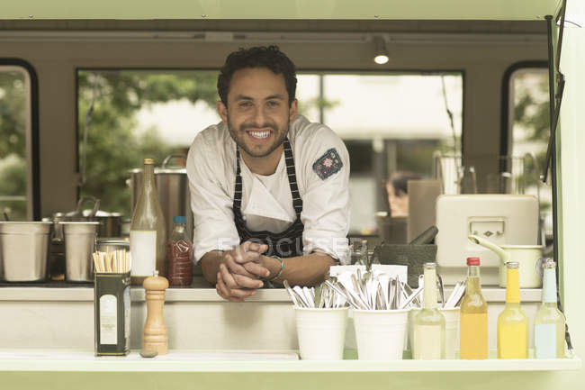 Portrait of smiling man in a food truck — Stock Photo