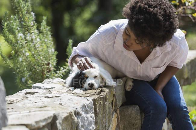 Femme caressant chien — Photo de stock