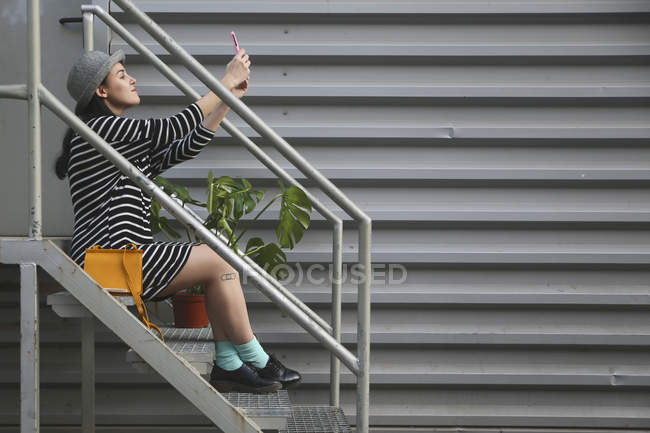 Young woman sitting onb stairs taking a selfie with smartphone — Stock Photo