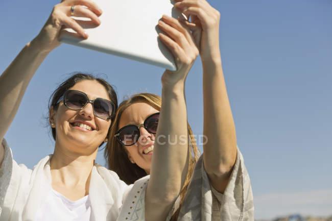 Duas mulheres sorridentes em óculos de sol tirando uma selfie em sol com tablet digital — Fotografia de Stock