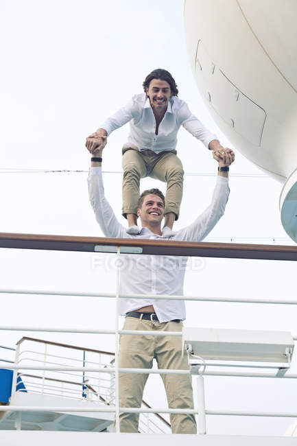 Two young men messing about on cruise ship, balancing on shoulders — Stock Photo