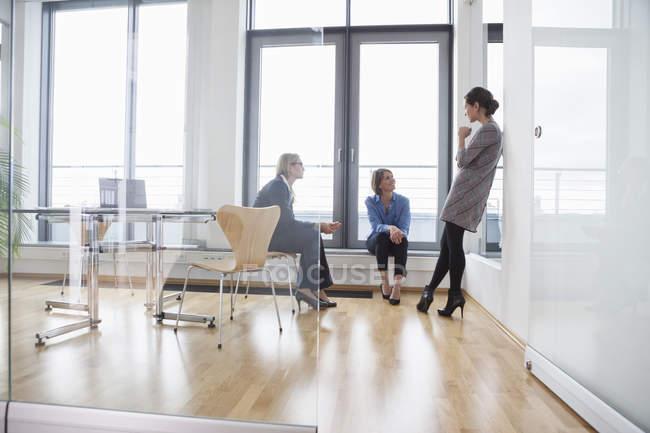 Tre donne d'affari che parlano alla finestra in un ufficio moderno — Foto stock