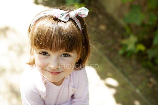 Portrait de petite fille souriante avec ruban de cheveux — Photo de stock