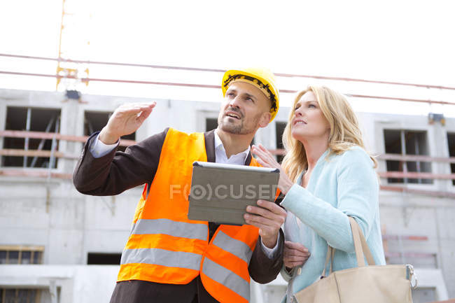 Man with hard hat talking to woman on construction site — Stock Photo