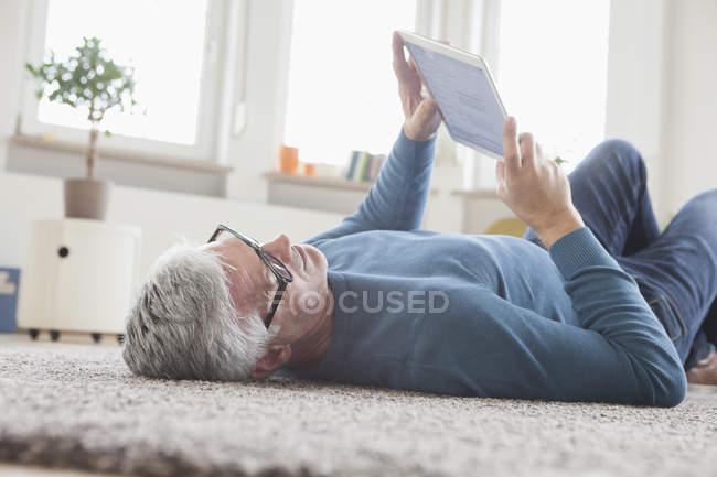 Homem maduro em casa deitado no chão usando tablet digital — Fotografia de Stock
