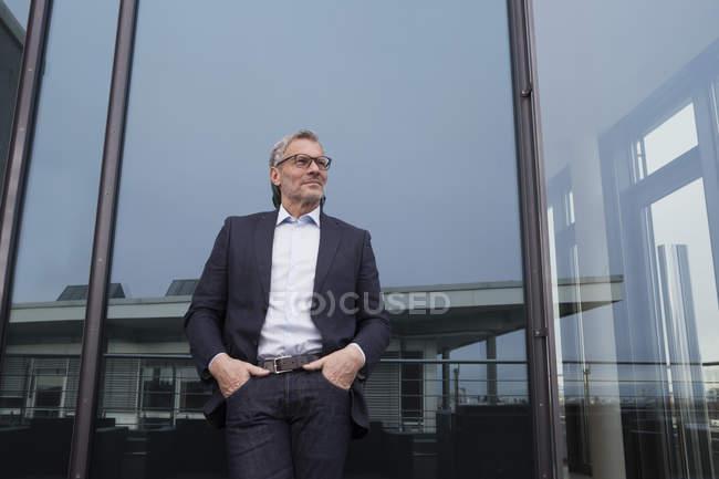 Erfolgreicher Geschäftsmann steht zufrieden auf Büroterrasse — Stockfoto