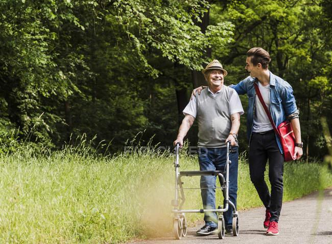 Heureux grand-père marchant avec son petit-fils dans la nature — Photo de stock