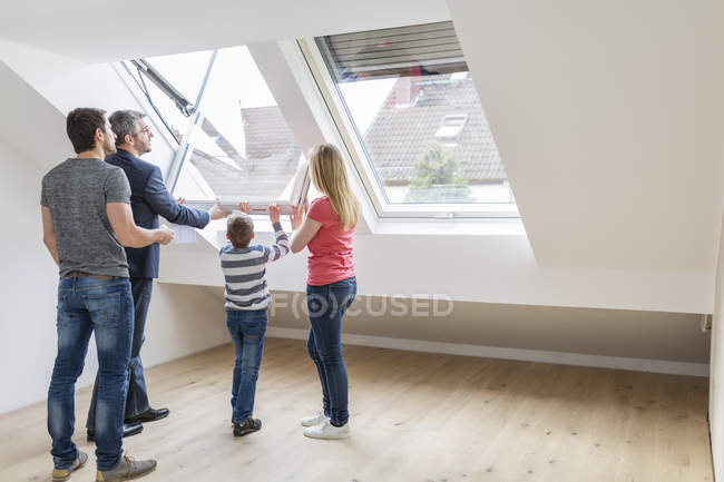 Family and estate agent opening rooflight — Stock Photo