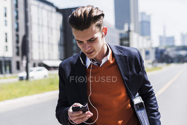 Junger Mann mit Handy und Ohrhörern unterwegs — Stockfoto