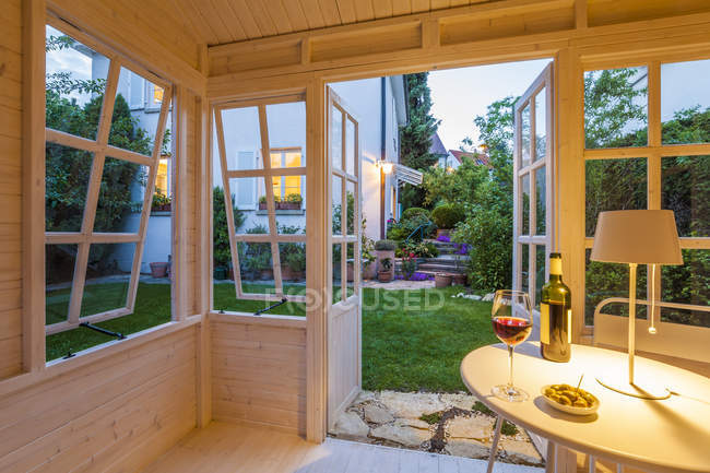 Red wine glass and bottle and bowl of olives on table in a garden shed — Stock Photo