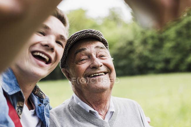 Grandfather and grandson taking selfie with smartphone — Stock Photo