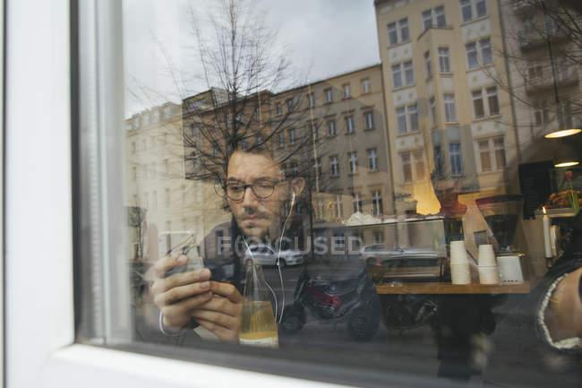 Человек в кафе за оконное стекло — стоковое фото